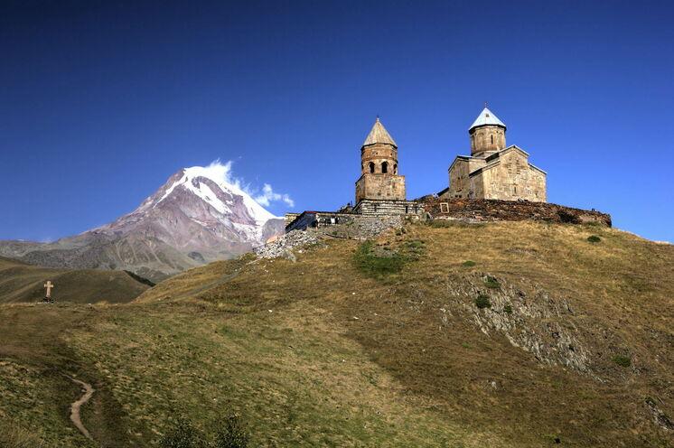 """Einsam im Hochgebirge liegt die Gergeti-Kirche, im Hintergrund """"grüßt"""" der Kasbek (5047 m)"""