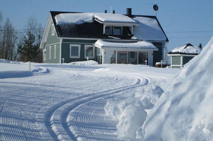 Finnische Wohnkultur. Viele Holzhäuser verfügen über einen Wintergarten, und wie hier in der Kleinstadt Muonio mit angeschlossener Loipe