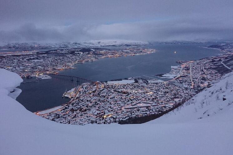 Der Blick von Tromsø´s Hausberg Storsteinen auf Tromsø zur Zeit der Polarnächte. Die gemeinsame Gondelfahrt zum Storsteinen ist im Reisepaket gleich mit dabei!