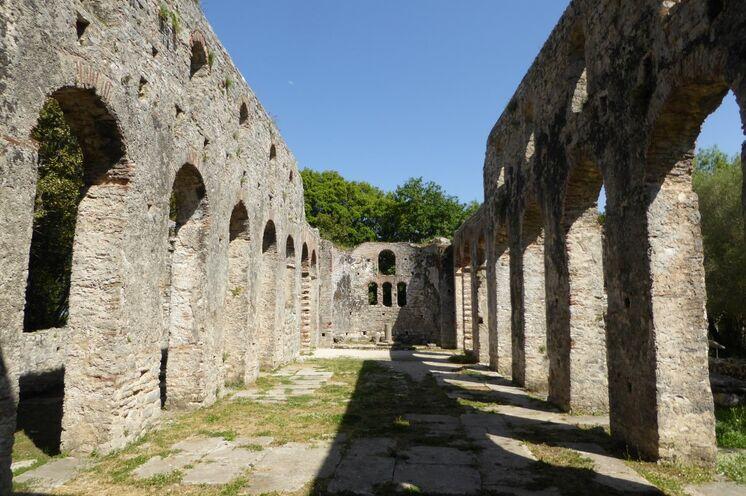 Hören Sie spannende Geschichten bei einer Führung durch die antike UNESCO-Weltkulturerbestätte Butrint; in Sichtweite die griechische Insel Korfu.