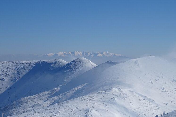 Über den schneebedeckten Gipfeln der Mala Fatra zeigen sich die Zweitausender der Hohen Tatra