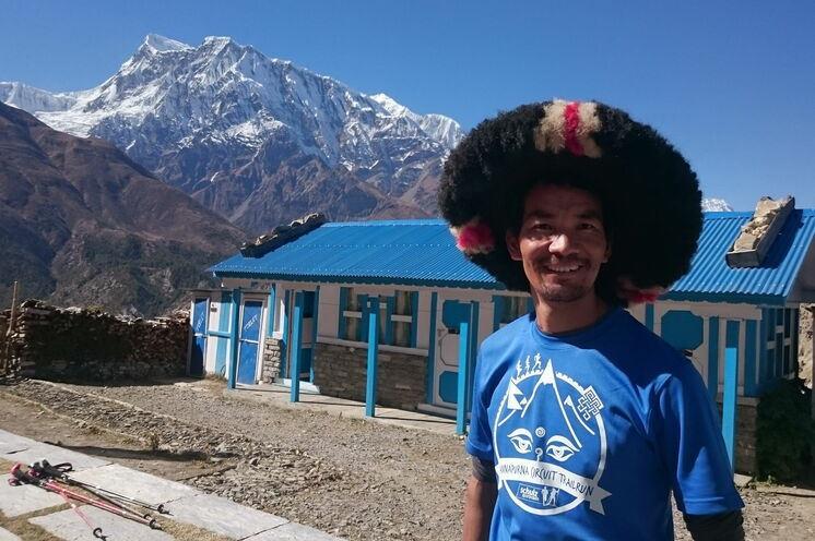 Reiseleiter Gelu Sherpa mit traditioneller Kopfbedeckung und dem Annapurna Circuit Trailrun-Teilnehmershirt
