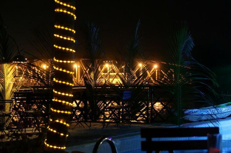 Eine Bar liegt direkt am Senegalfluß mit dem Blick auf die stadtprägende Brücke.