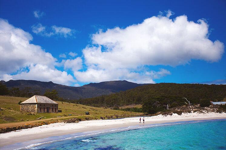 Zu Fuß unterwegs auf der Nationalparksinsel Maria Island: türkisblaues Wasser, weiße Strände, Wälder und Granitfelsen.