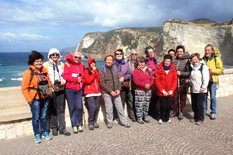 Eine glückliche Wandergruppe mit traumhaftem Steilküstenpanorama.