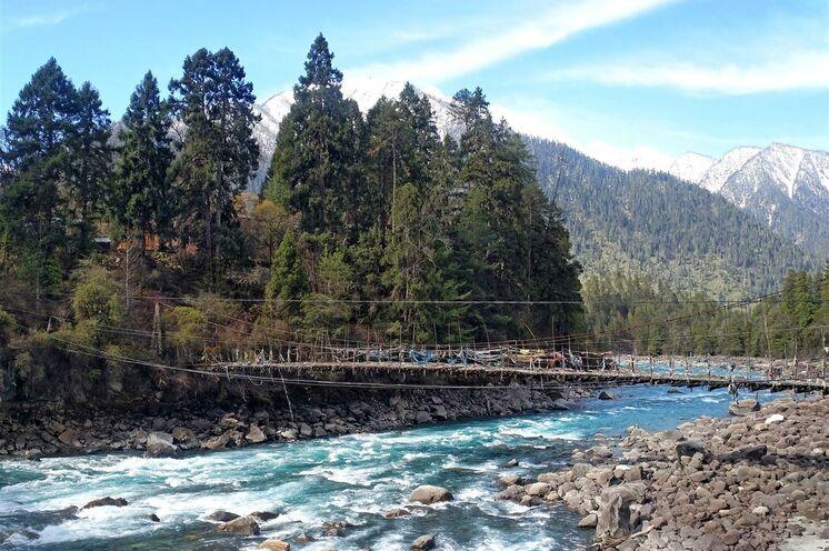 Grüne Wälder und reißende Flüsse sind ständige Begleiter auf einer Reise durch Osttibet