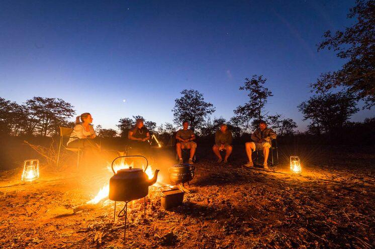 Beim Lagerfeuer am Abend lassen Sie den Tag ausklingen