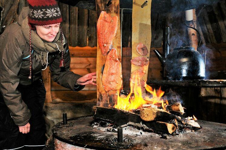 Eine der feinsten finnischen Spezialitäten genießen Sie nach Ihrem Rauchsaunagang: Feuerlachs direkt am Feuer