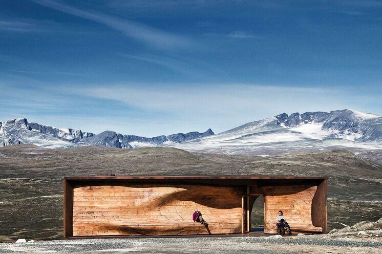 Eine Reihe von Steinplatten erzählt die 10000-jährige Geschichte vom Dovrefjell auf Ihrem Weg zum international ausgezeichneten Snøhetta-Aussichtspunkt mit seiner organischen und welligen Holzform