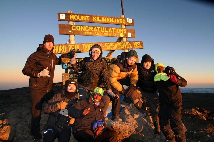 Das große Ziel: der Uhuru-Peak. Beste Laune mit Gipfelschild im Rücken und Sonne im Gesicht.