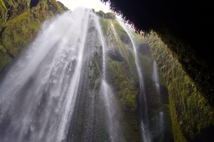 Versteckter Wasserfall im moosbedeckten Felsen - ein Stopp der unbedingtsein muss und nass wird.